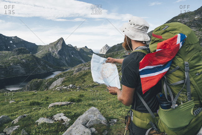 Norway- Lofoten- Moskenesoy- Man with backpack and Norwegian flag holding map
