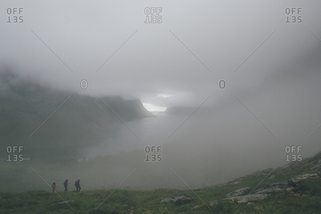 Norway- Lofoten- Moskenesoy- Three men hiking in the fog