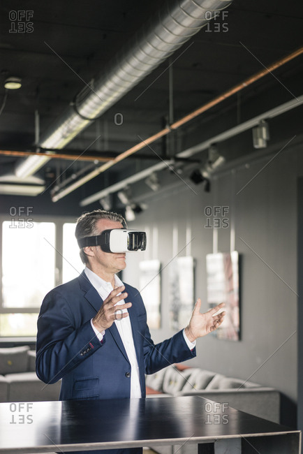 Mature businessman wearing VR glasses