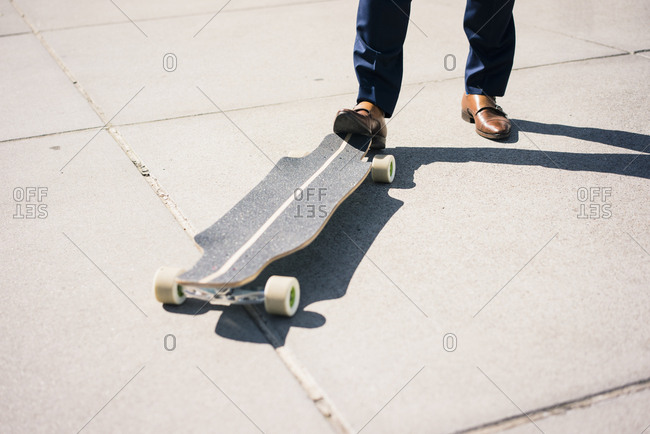 Businessman with longboard outdoors