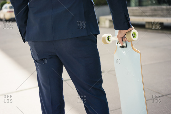 Businessman holding longboard outdoors