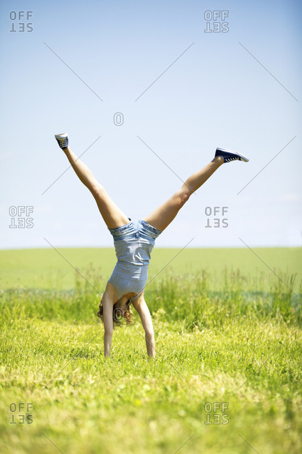 Young woman doing handstand on meadow