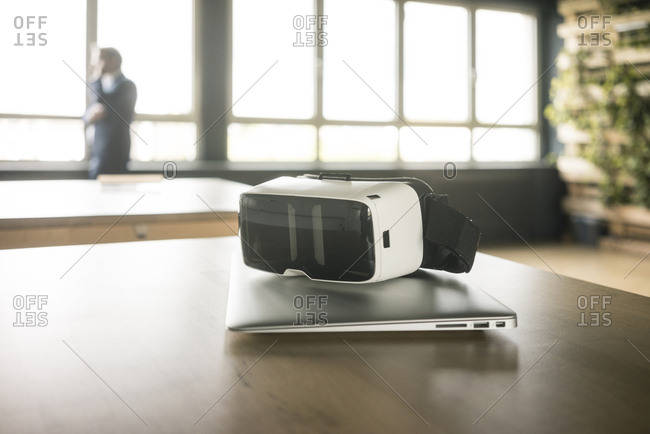 VR glasses and laptop on table in office with businessman in background