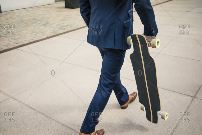 Businessman walking with longboard outdoors