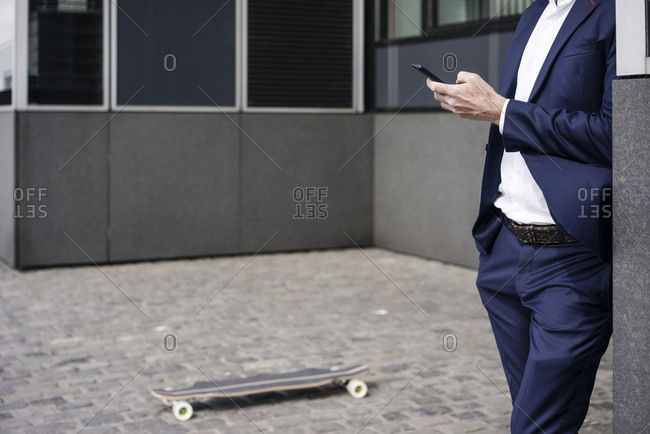 Businessman with longboard using cell phone outdoors