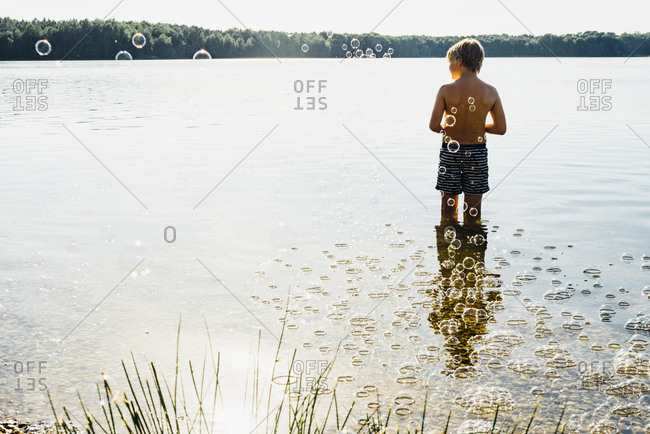 Boy in a lake surrounded by soap bubbles