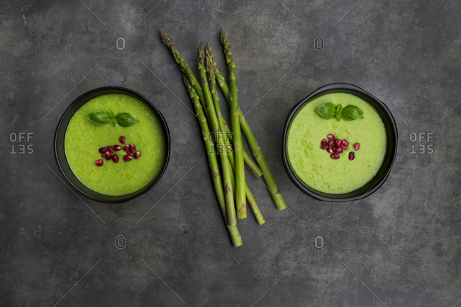 Green asparagus soup with pomegranate seeds and basil