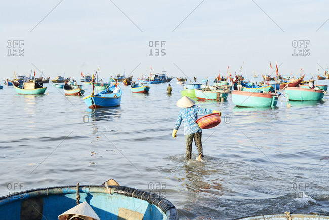 Vietnamese woman carrying seafood at seashore for sell with wholesale buyer at clandestine fishing market
