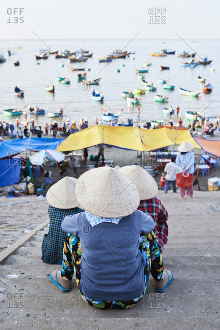 Three faceless senior women observing activity at Mui Ne fishing market at early morning when fishers arrive to harbor with seafood and fish goods