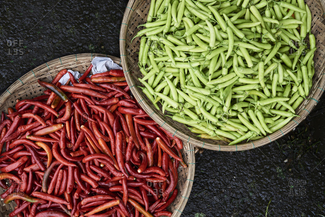 Red and green chili peppers placed in different baskets in a local market