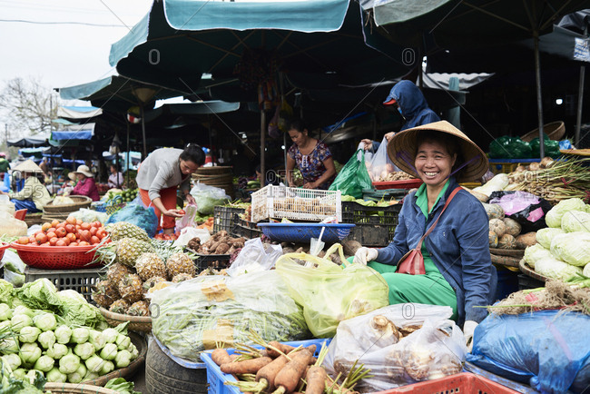Hue, Vietnam - January 26, 2018: Dong Ba market with many fresh fruit and vegetables and a smiley local seller