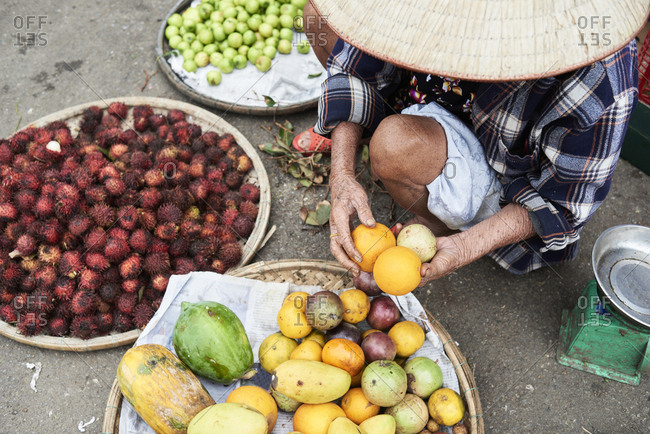 Faceless vietnamese senior vendor picking oranges from a basket in a local market