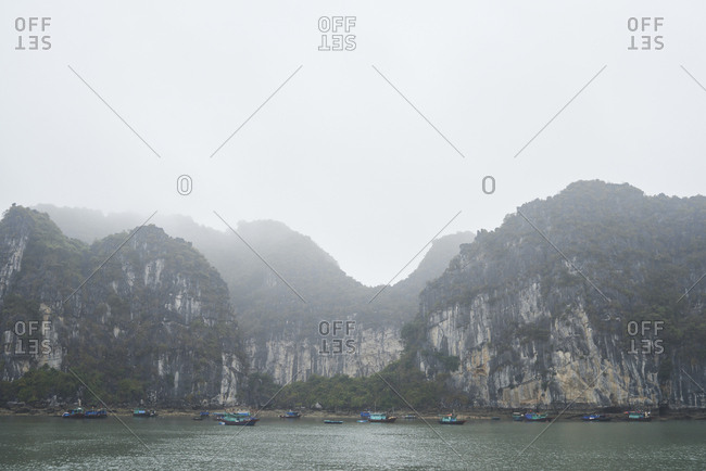Panorama view of fishing boats moored at the coast of Ha Long Bay, Vietnam in cloudy mystic day