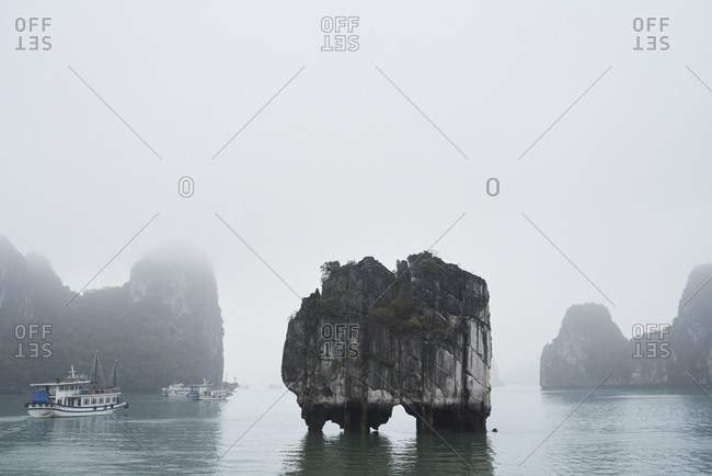 Ha Long Bay minimal landscape in cloudy and foggy day against passenger cruises passing by