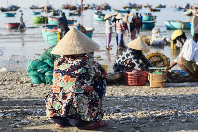 Mui Ne, Vietnam - January 7, 2018: Faceless vietnamese woman wearing hat and sitting squat asian position watching activity at seashore of fishing market