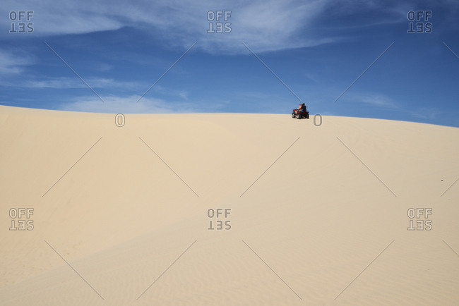 Full length view of group of tourists driving red squad at the white sand dunes against blue sky in Mui Ne