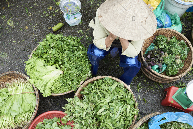 Tired faceless vendor sitting in a chair against green vegetables placed in baskets in local market
