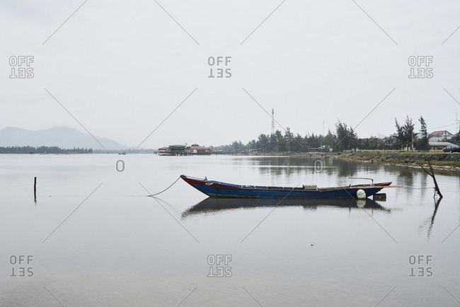 Relaxing landscape with rowboat moored in the middle of lake in Vietnam