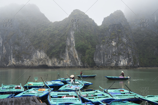 Unrecognizable local vietnamese working in fishing boats at Ha Long Bay coast in cloudy and rainy day