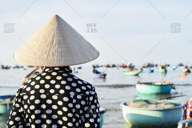 Faceless vietnamese woman wearing hat watching activity at seashore of fishing market