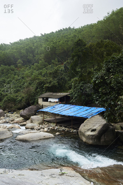 Foot of a waterfall in mountain jungle with cabin in the middle of nowhere