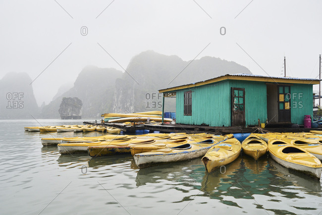 Local business floating platform with many kayaks available for rent against Ha Long Bay landscape