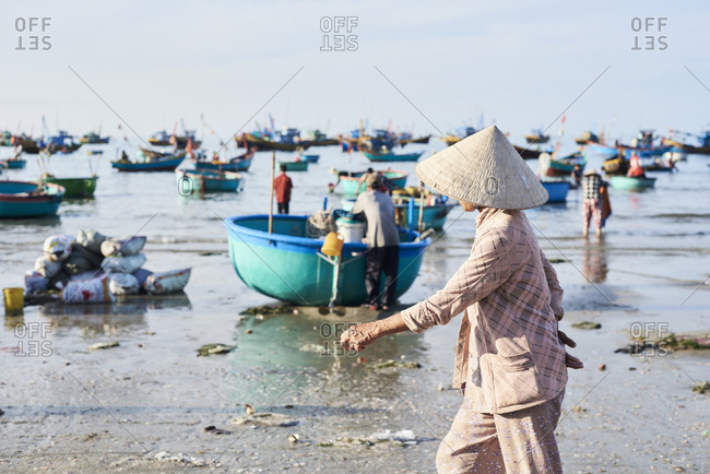 Faceless vietnamese woman wearing hat walking around seashore while supervising activity at clandestine fishing market