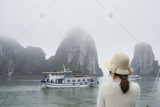 Unrecognizable asian tourist wearing hat amazed by Ha Long Bay landscape