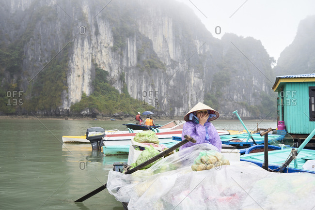 Ha Long Bay, Vietnam - February 27, 2018: Local vietnamese woman wearing hat sitting inside rowboat carrying goods and food at a floating fishing village