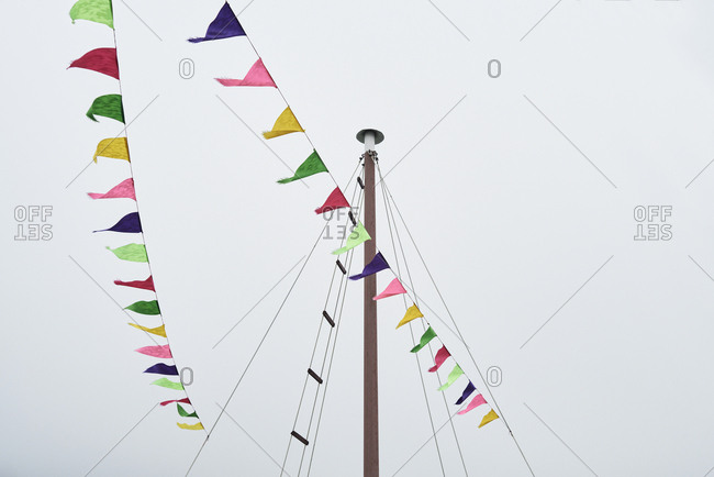 Colorful paper bunting hang from cable in cruise on a cloudy and mystic day