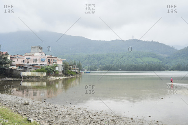 Scenic view of lake with charming old house and unrecognizable fisher on the water against mountains