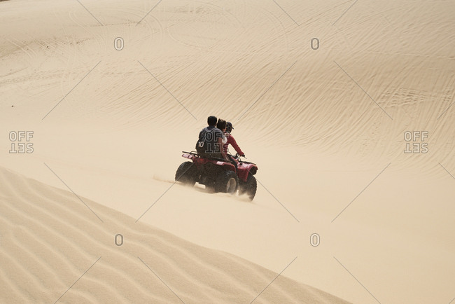 Tour guide driving red squad with tourists at the white sand dunes in Mui Ne