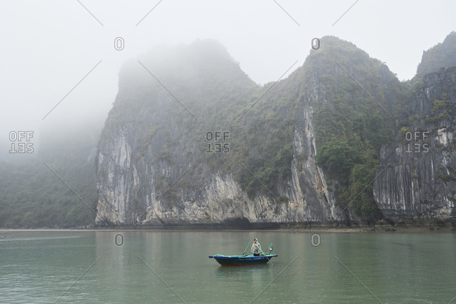 Ha Long Bay, Vietnam - February 27, 2018: Local tour guide inside rowboat standing while raining