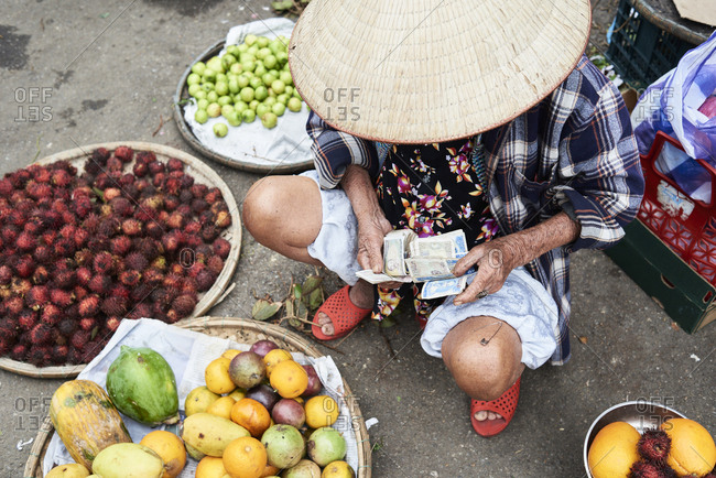 Hue, Vietnam - January 26, 2018: Vietnamese elderly vendor counting notes of money in a local market