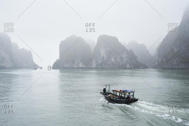 Ha Long Bay, Vietnam - February 27, 2018: Local fishing rowboat cruising towards Ha Long Bay harbor