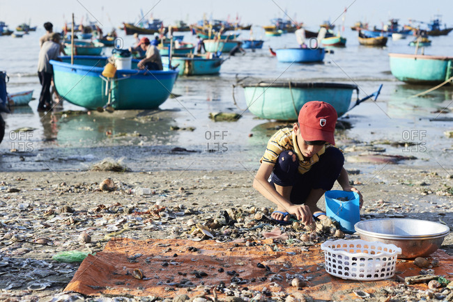 Mui Ne, Vietnam - January 7, 2018: Kid playing with remains of seafood at fishing market in the morning