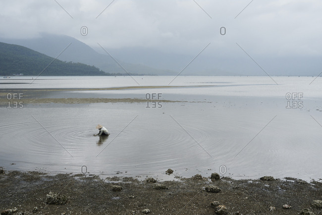 Faceless woman fishing clamshells in lake with hat against mountain landscape
