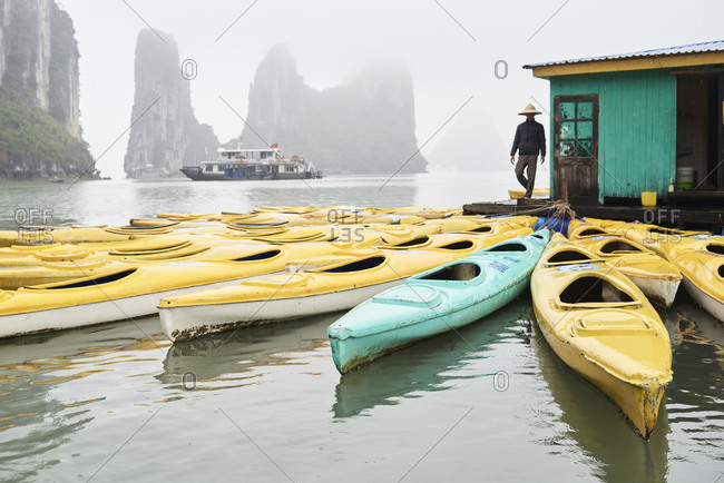 Local vietnamese businessman walking through platform of floating village with many kayaks available for rent