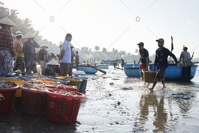 Mui Ne, Vietnam - January 7, 2018: Fishermen carrying seafood in basket at seashore for sell with wholesale buyer at clandestine fishing market