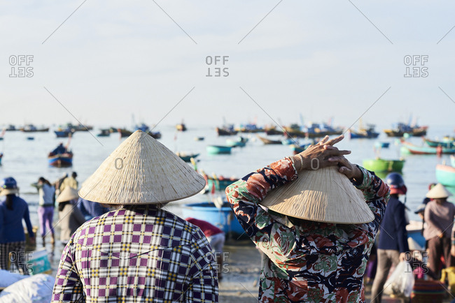 Faceless vietnamese women wearing hat watching activity at seashore of fishing market