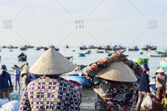 Faceless vietnamese women wearing hat watching activity at seashore of fishing market