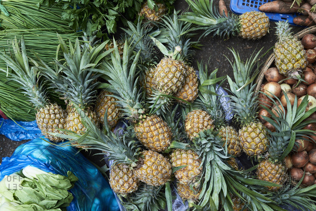 Messy view from above of pineapples, onion and lettuce placed randomly in an urban market