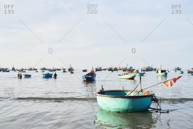 Panorama view of Mui Ne fishing market harbor with plenty of boats moored