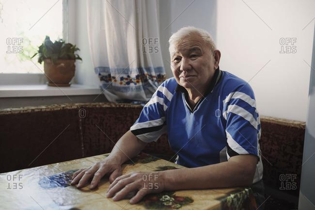 Pensive senior adult man sitting at table