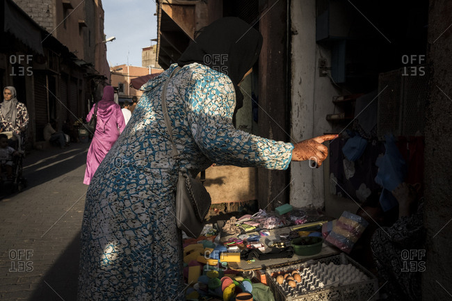 Marrakech, Morocco - September 16, 2017: Woman with hand covered with henna talking with the seller on a grocery store