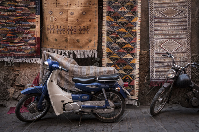Marrakech, Morocco - September 17, 2017: Bikes parked on the street next to rugs on sale