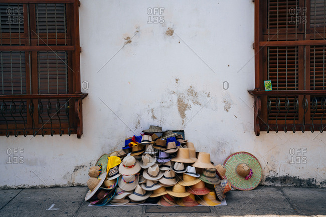 Large stack of miscellaneous hats for sale on side of road