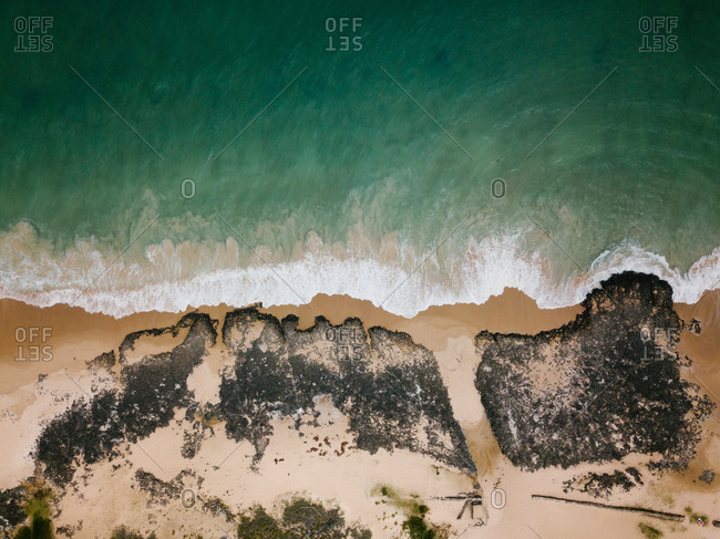 Aerial view of gentle tide on exotic beach