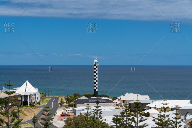 High angle view of small beach town with lighthouse in front of ocean
