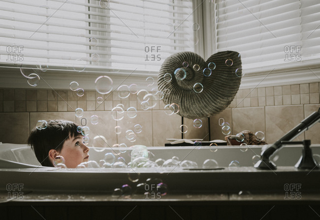 Boy looking at bubbles while taking bath in bathtub